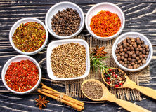Colorful aromatic Indian spices and herbs on an old oak wooden deep blue board Royalty Free Stock Image