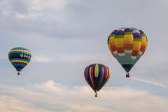 Colorful array of hot air balloons float through the sky at dusk at Warren County Farmer`s Fair, Harmony, New Jersey, on 8/1/17 Stock Images