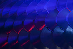 Colorful Array of Vinyl Records. Several vinyl records overlapping in an organized array and lit with red, blue, purple and white lights Royalty Free Stock Image