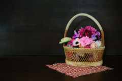Colorful artificial flowers made from cloth in basket on wooden Stock Image