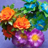 Colorful artificial flowers purple background,. Spring bouquet Stock Image