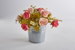 Colorful artificial rose flowers in pot on white background stock photo