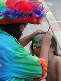 Colorful artist doing face paint for child, Royalty Free Stock Photo