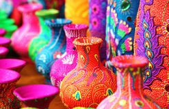 Colorful artistic pots or flower vases in vibrant colors. These handmade color painted vessels are in vivid colors like orange, pink, blue, etc Royalty Free Stock Photo