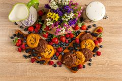 Colorful assorted mix of wild berries, brown cookies, milk and flowers royalty free stock image