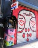 Colorful ATM Machine. Next to graffiti Stock Photos