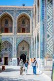 Colorful atrium in Samarkand Registan, Uzbekistan. SAMARKAND, UZBEKISTAN - AUGUST 8: People walking in colorful atrium full of mosaics, Registan, famous landmark Royalty Free Stock Photo