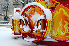 Colorful attraction covered by snow in winter park during snowfa Stock Photos