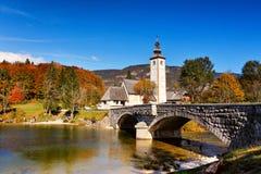 Colorful autumn day in ancient village with old bridge and churc. H. Church tower and stone bridge at Lake Bohinj in alpine village Ribicev Laz, Slovenia Stock Photos