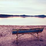 Colorful autumn evening. Empty wooden bench on beach of lake. Royalty Free Stock Photo
