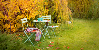 Colorful autumn garden nook with hot tea and blanket stock photos