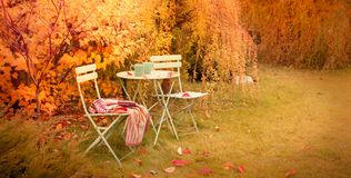 Colorful autumn garden nook with hot tea and blanket royalty free stock photos
