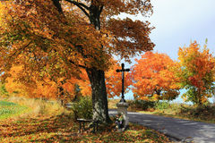 Colorful autumn Landscape with Crucifix and blue Sky Royalty Free Stock Images