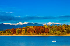 Colorful Autumn landscape with lake and a boat. Royalty Free Stock Photo