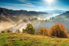 Colorful autumn landscape with misty valley,Holbav,Transylvania,Romania,Europe. Stunning autumn nature with misty landscape,Holbav village,Carpathians Stock Photo