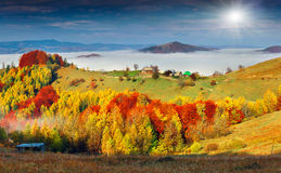 Colorful autumn landscape in the mountain village. Foggy morning Royalty Free Stock Photos