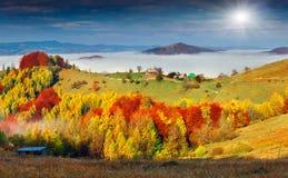 Colorful autumn landscape in the mountain village. Foggy morning. In the Carpathian mountains. Sokilsky ridge, Ukraine, Europe Royalty Free Stock Photos
