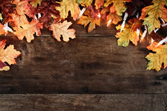 Colorful Autumn Leaves and Lights over Wooden Background. Rustic fall background of colorful autumn leaves and decorative lights over a rustic wooden background Stock Image