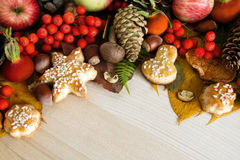 Colorful autumn leaves, mushrooms, rose hips, rowanberry, apples, nuts, cones and cookies on the wooden background. Stock Photo