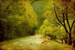 Colorful autumn in the mountains. Vintage photo of curving road in autumn forest Royalty Free Stock Image