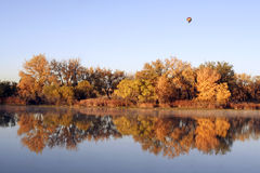 Colorful Autumn Pond. A hot air balloon floats over a tranquil pond and the changing colors of vegetation during the autumn season Stock Images