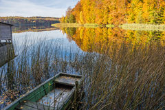 Colorful Autumn Scenery. Autumn landscape in Brandenburg, Germany with lake, boat, and colorful  trees Stock Photo