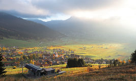 Colorful autumn scenery of Lermoos, a Tyrolean village on green fields bathed in golden sun light Royalty Free Stock Images