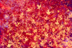 Colorful autumn season spiral composed maple leaves on blurry. Bright golden red glitteer,bokeh.Modern simple flat sign. Trendy valentine decoration symbol for Stock Photography