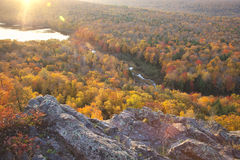 Colorful autumn trees in early morning light. Autumn trees in full color with rocky cliff edge at Lake of the Clouds Michigan. Taken at sunrise royalty free stock images