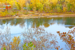 Colorful autumn trees foliage and river waters in the park. Stock Images