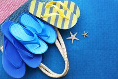 Colorful baby flip flops and bag. On blue background stock photo