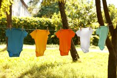 Colorful baby onesies hanging on clothes line. Outside stock images