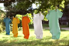 Colorful baby onesies hanging on clothes line. Outside royalty free stock photography