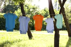 Colorful baby onesies hanging on clothes line. Outside stock photos