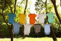 Colorful baby onesies hanging on clothes lines. Outside stock photo