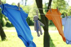 Colorful baby onesies and toy bear hanging on clothes line. Outside stock images