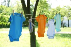 Colorful baby onesies and toy bear hanging on clothes line. Outside stock photography