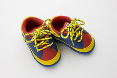 Colorful baby shoes. A pair of red, blue and yellow baby shoes on white Royalty Free Stock Photo