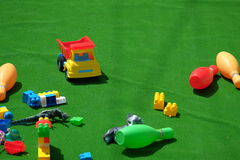 Colorful baby toys from plastic. Colorful plastic toys on the green carpet stock image
