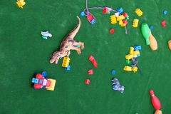 Colorful baby toys from plastic. Colorful plastic toys on the green carpet royalty free stock image