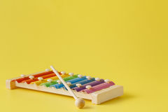 Colorful baby xylophone with stick. On yellow royalty free stock photos