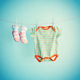 Colorful background for baby girl with two pink socks and body suit with copy space. Stock Photography
