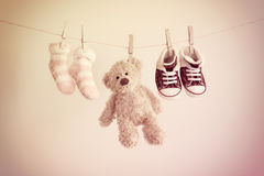 Colorful background for baby girl with two pink socks, sneakers and teddy bear with copy space. Stock Photo