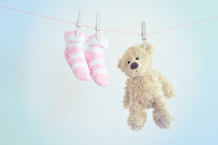 Colorful background for baby girl with two pink socks and teddy bear with copy space. Royalty Free Stock Photography