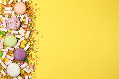 A colorful background with candies, marshmallows and macaroons on a yellow background. Sweets stock photo