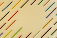 Colorful background with many crayons pastels lined up on yellow Royalty Free Stock Photo
