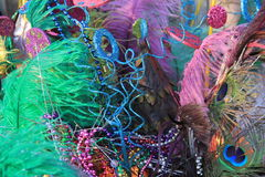 Colorful background of Mardi Gras beads, feathers and masks. Bright and colorful backdrop of Mardi Gras feathers, beads and masks, sure signs that a festive stock image