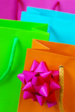 Colorful Bags. Background of colorful paper bags with a bow in the foreground Royalty Free Stock Image