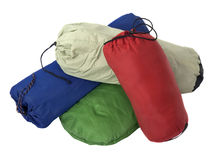 Colorful bags with camping equipment. A pile of colorful bags with camping equipment (tent, sleeping bag, pad) isolated on white royalty free stock image