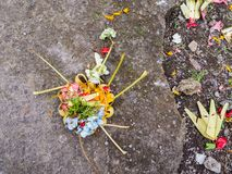 Colorful Balinese canang sari offering with flowers on the stre Royalty Free Stock Photography